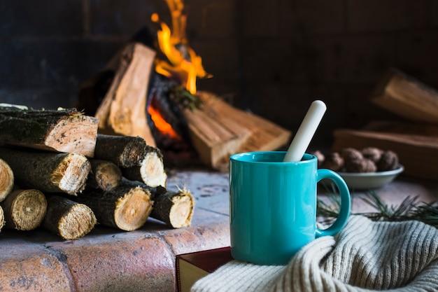 Mug and blanket near fireplace Free Photo
