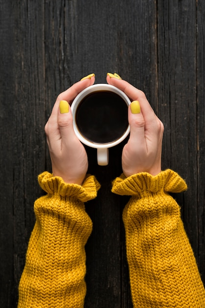 Mug of coffee in a female hands. top view Premium Photo