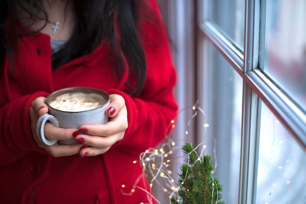 Mug of coffee with marshmallow in the hands of a woman in a red sweater, near the window Premium Photo