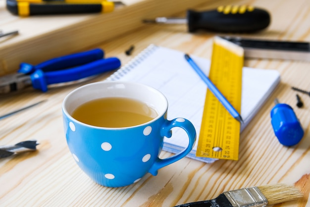 Mug, drawings and construction tools for building a house or apartment renovation. Premium Photo