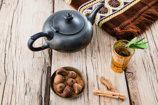 Mug of drink near teapot, mat and sweets on board Free Photo