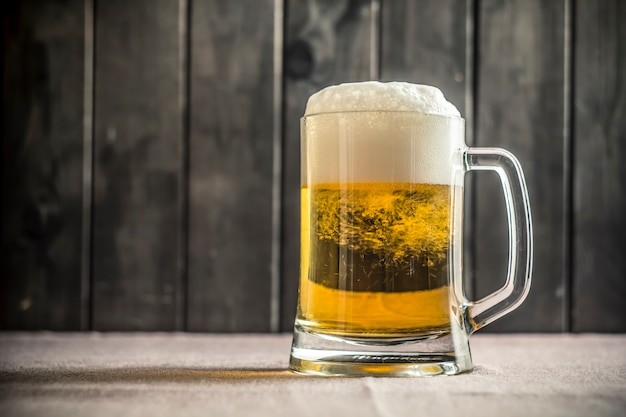 A mug of fresh beer on the pub's table. Premium Photo