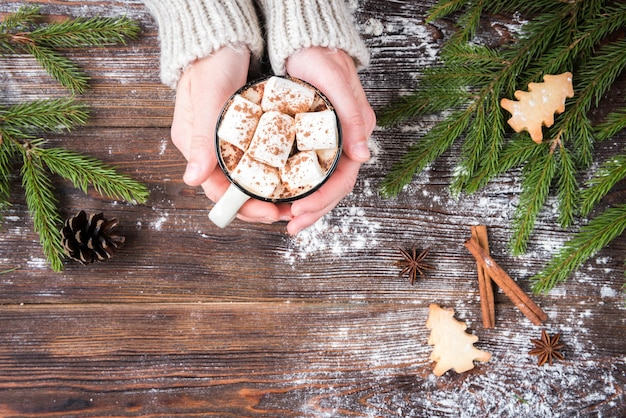 Mug of hot chocolate with marshmallow, spices, christmas ginger cookies, fir branches and cones on dark wooden background. copy space for text. christmas wallpaper, card. Premium Photo