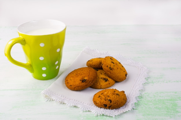Mug of milk and cookies on white plate Premium Photo