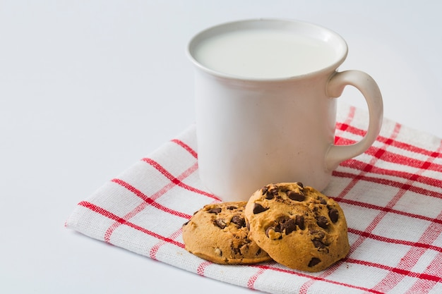 Mug of milk with cookies on napkin over the white background Free Photo