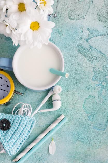 A mug of milk with straw, headphones and holder Premium Photo