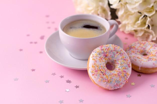 ホットカプチーノとピンクの花を持つ2つのドーナツのマグカップ Premium写真