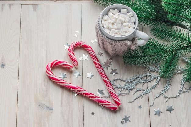 木製のテーブルの上のクリスマスの装飾に囲まれたマシュマロとキャンディケインのマグカップ 無料写真