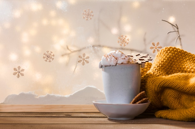 Mug on plate with cookies near scarf on wood table near bank of snow and fairy lights Free Photo