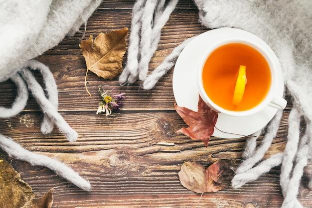 Mug of tea and scarf on table Free Photo