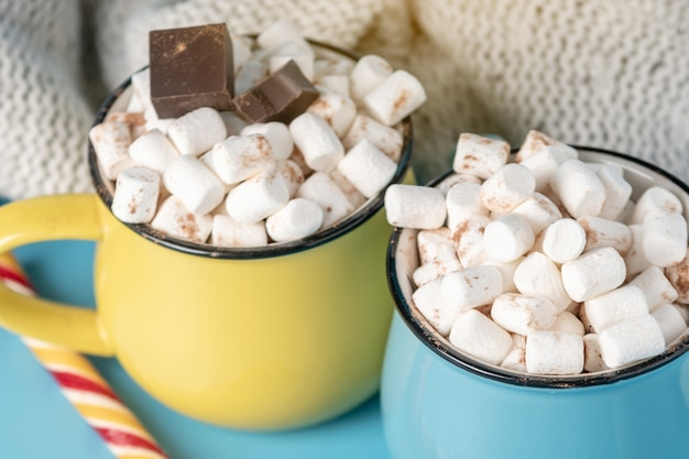 Mugs of hot chocolate with marshmallows on top and stick a lollipop. Premium Photo
