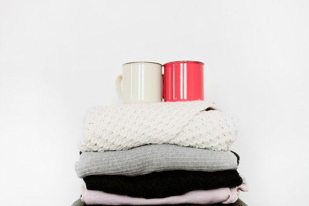 Mugs on stack of warm clothes Free Photo