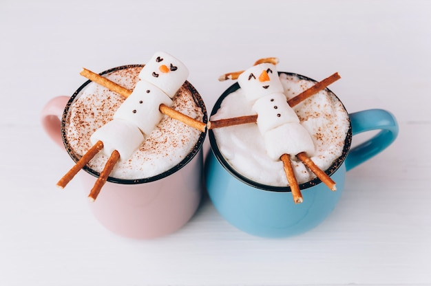 Mugs with hot chocolate in which the men from the marshmallow relax. concept of a couple Premium Photo