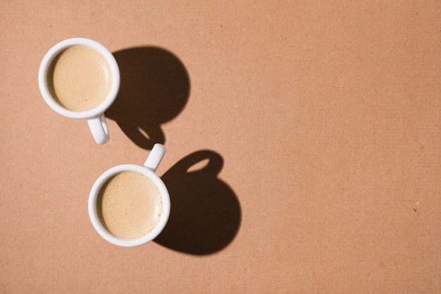 Mugs with hot coffee and shadows Free Photo