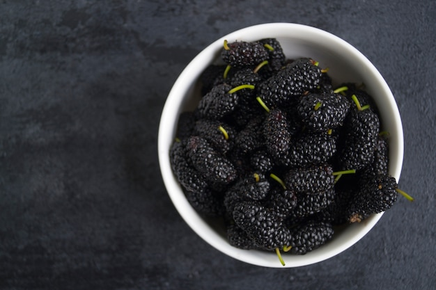 The mulberry in a white bowl on the black table. Premium Photo