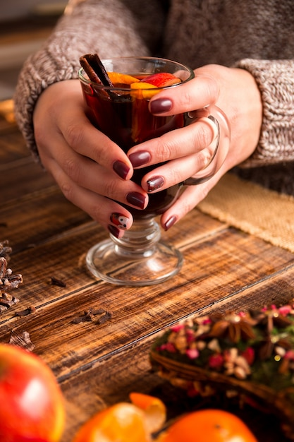 Mulled wine in female hands, spices and fruit ingredients, Premium Photo
