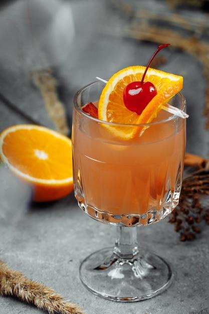 リンゴオレンジとシナモンを添えたグラスグラスのグリューワイン。灰色のテーブルの上の熱いクリスマスドリンク Premium写真