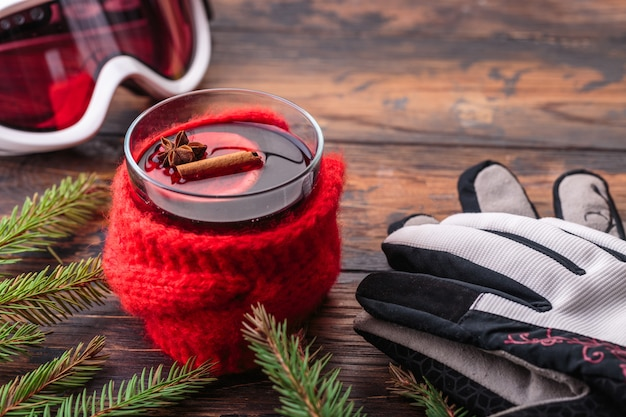 Mulled wine in woman hands cozy home concept ingredients winter sport goggles ski gloves Premium Photo
