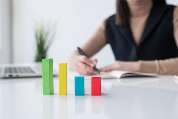 Многоцветная кубическая диаграмма на столе на фоне бухгалтера или брокера, записывающего финансовый анализ в тетрадке Premium Фотографии