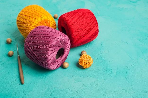 Multi color yarn balls on mint background Premium Photo