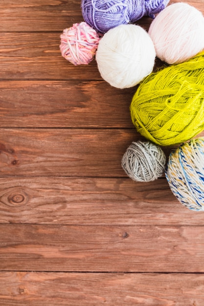 Multi colored ball of yarns on wooden background Free Photo