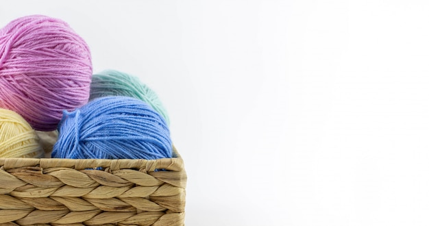 Multi-colored balls of yarn for knitting lie in a wicker basket Premium Photo