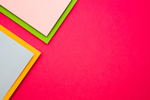 Multi colored cardboard papers on pink background Free Photo