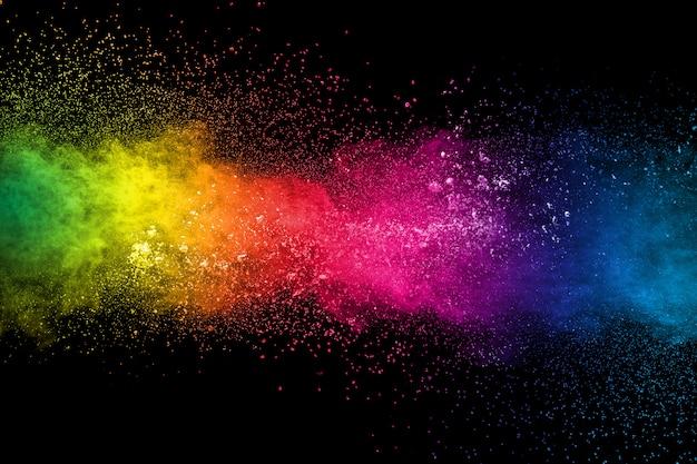 Multi colored dust splash on black background.painted holi. Premium Photo