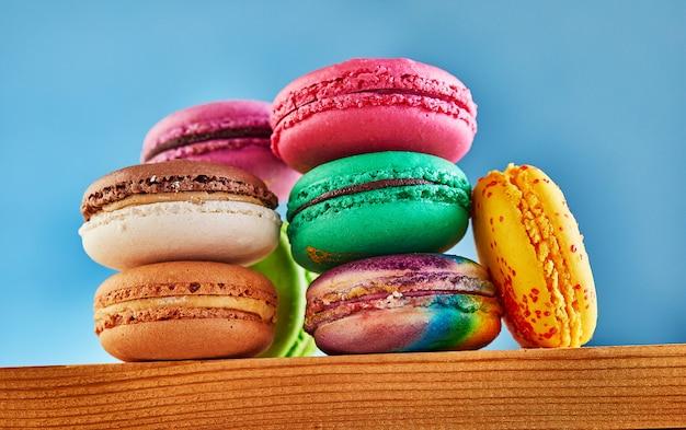 Разноцветные макаруны сложены в стопку на деревянной поверхности Premium Фотографии