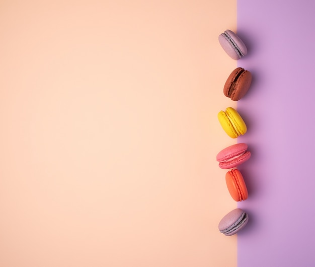 Multi colored macarons with cream on a purple beige background, flat lay Premium Photo