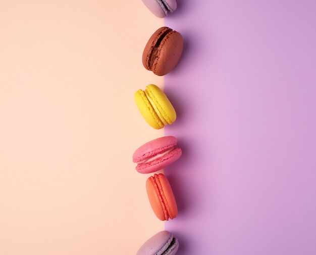 Multi colored macarons with cream on a purple beige background Premium Photo