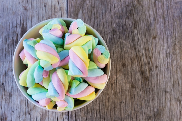 Multi-colored marshmallow twist in a bowl on a wooden table. Premium Photo