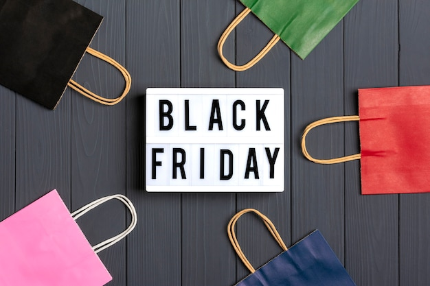 Multi-colored packaging bags, gift boxes lightbox with text black friday on dark gray surface flat lay Premium Photo