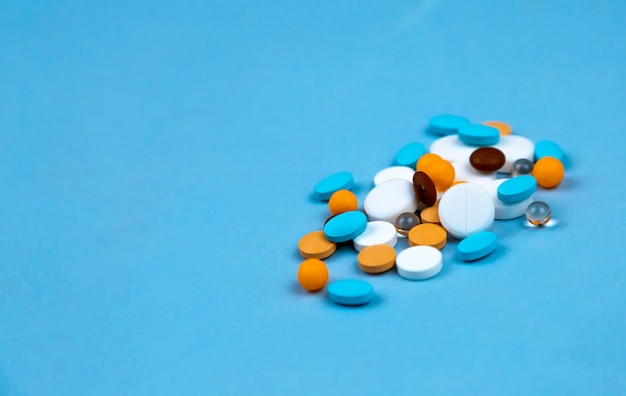 Multi-colored pills on a blue background close-up, Premium Photo