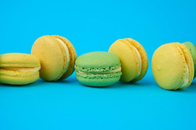 Разноцветные круглые печеные пирожные с макаронами на голубом фоне, десерт стоит в ряд Premium Фотографии