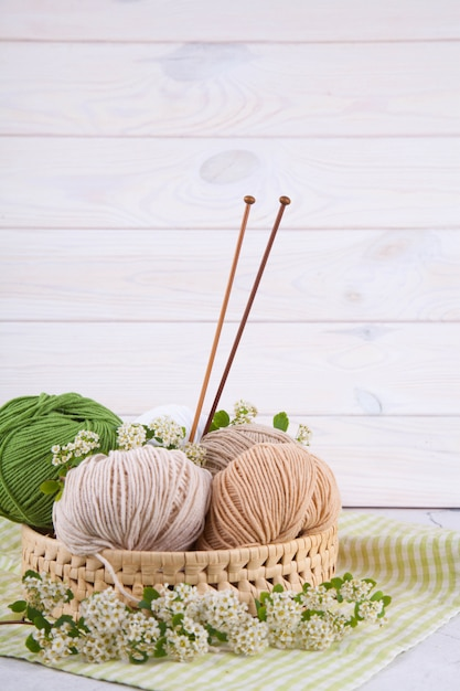 Multi-colored tangles of yarn in a wicker basket on the table. japanese style wabi sabi. home comfort, handicraft. Premium Photo