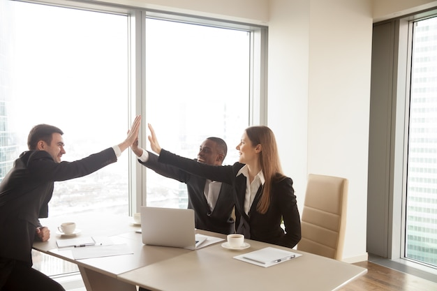 Multi-ethnic business partners giving high five on meeting, cele Free Photo