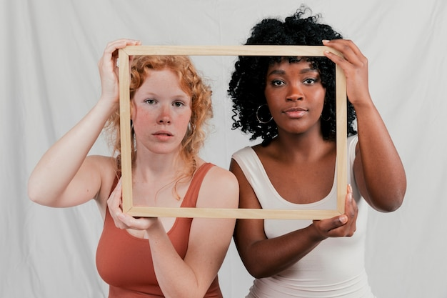 Multi ethnic female friend looking at camera through wooden frame against grey backdrop Free Photo