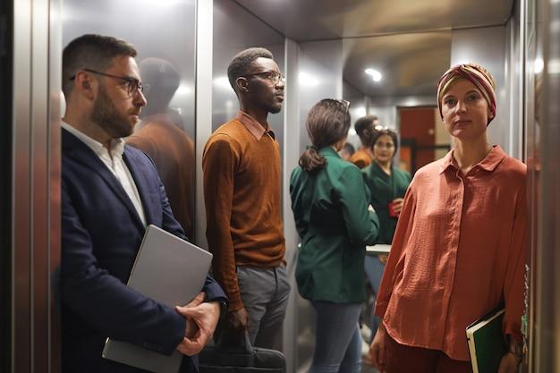 문을 열고 엘리베이터에 서있는 사업 사람들의 다민족 그룹, 전경에서 젊은 여자에 초점, 복사 공간 프리미엄 사진
