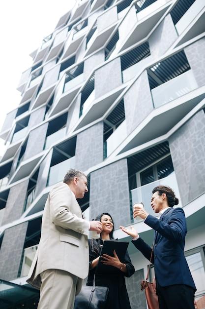 近代的なオフィスビルの外に立ってアイデアを議論するビジネスマンの多民族グループ Premium写真
