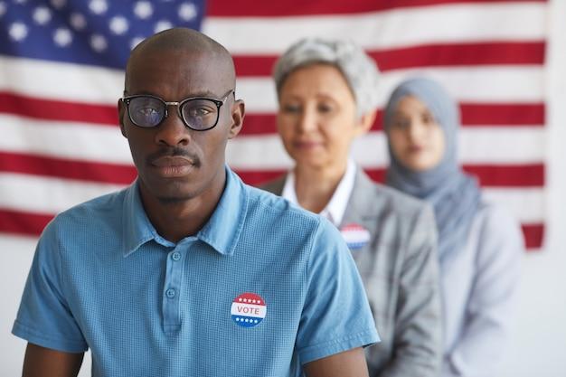 선거 당일 투표소에서 사람들의 다민족 그룹, 내가 투표 한 스티커, 복사 공간이있는 아프리카 계 미국인 남자에 초점 프리미엄 사진