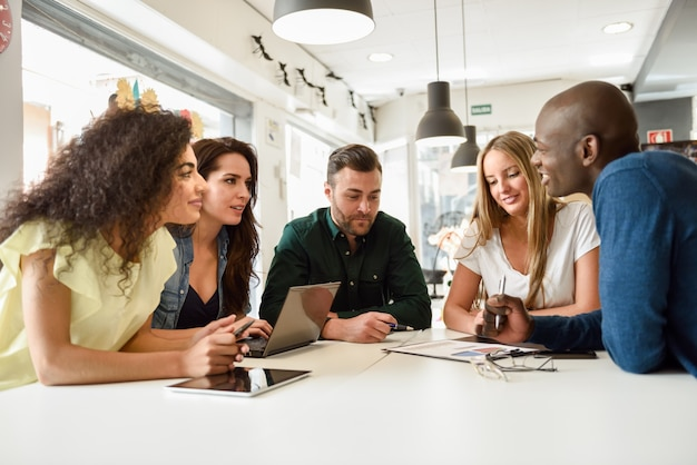 Multi-ethnic group of young people studying together on white de Free Photo