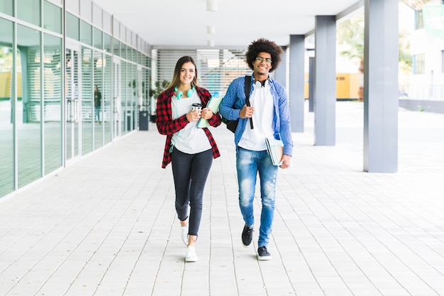 Multi ethnic male and female students walking together in university campus Free Photo