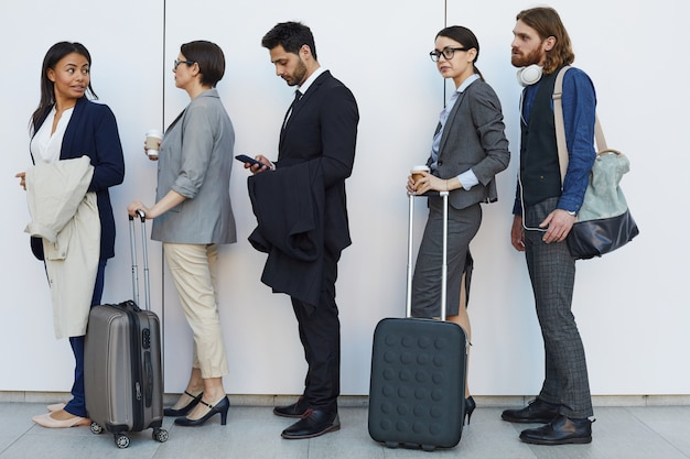 Multi-ethnic people with luggage standing in line Premium Photo