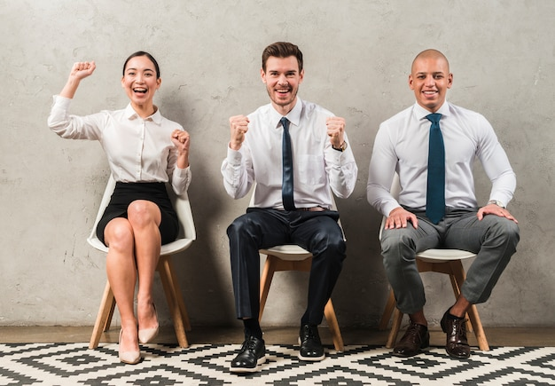 Multi ethnic young businessman and businesswoman sitting on chair celebrating their success Free Photo