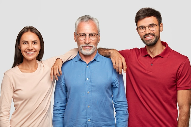 Multi generation concept. family portrait of mature wrinkled man dressed in stylish shirt, stands between his daughter and son Free Photo