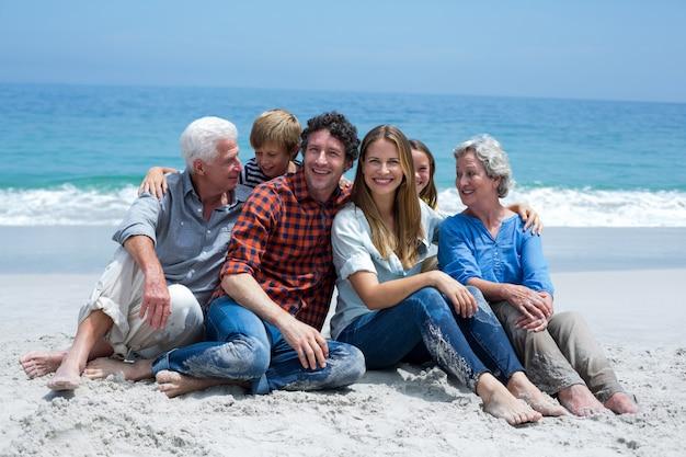Multi-generation family smiling relaxing at sea shore Premium Photo