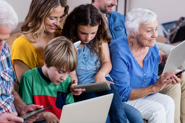 Multi-generation family using a laptop, tablet and phone Premium Photo
