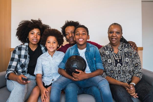 自宅でサッカーの試合を見ている多世代家族。 無料写真