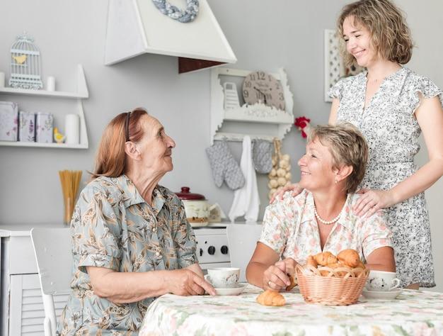 台所で朝食を食べて多世代女性 無料写真